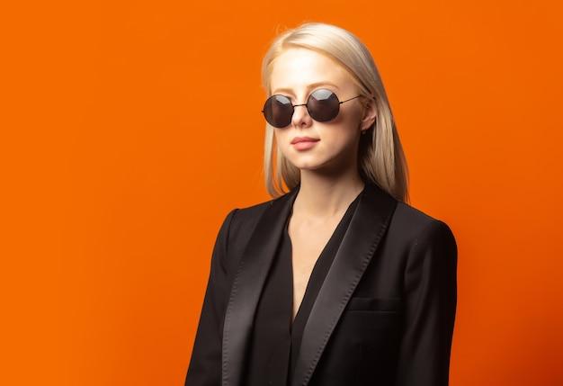 Stijlblond in zwarte blazer en zonnebril op een uitbundige oranje achtergrond