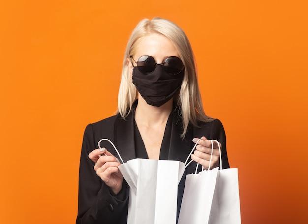 Stijlblond in zwarte blazer met boodschappentassen op een uitbundige oranje achtergrond