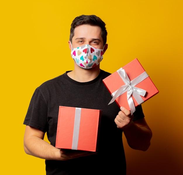 Stijlman in gezichtsmasker met geschenkdoos