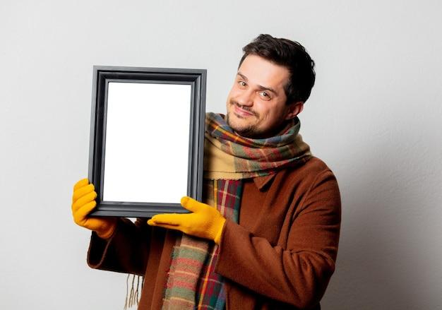 Stijlman in jas en sjaal met fotolijst