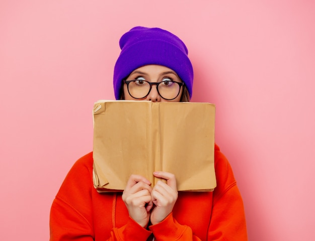 Stijlmeisje in oranje hoodie en purpere hoed met boek op roze muur