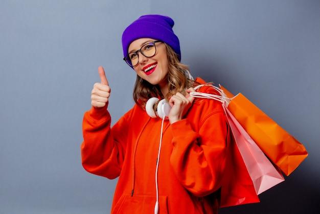 Stijlmeisje in oranje hoodie en purpere hoed met het winkelen zakken op grijze muur