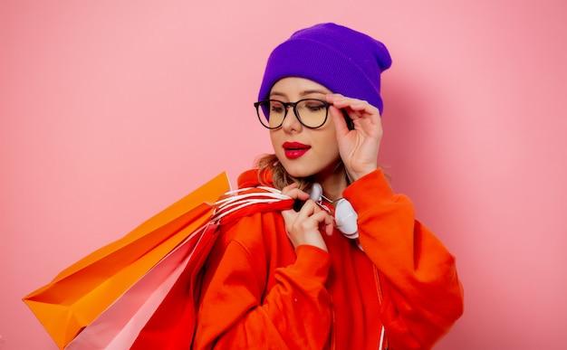 Stijlmeisje in oranje hoodie en purpere hoed met het winkelen zakken op roze muur