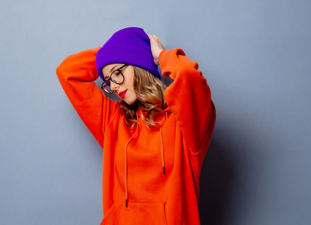 Stijlmeisje in oranje hoodie en purpere hoed op grijze muur