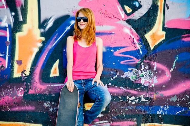 Stijlmeisje met skateboard dichtbij graffitimuur.