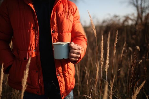 Stijlmens in donsjack met kop van koffie