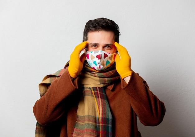 Stijlmens in jas en sjaal met gezichtsmasker