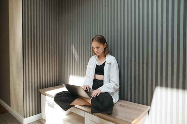 Stijlvol aantrekkelijk meisje zit op een nachtkastje een stijlvol appartement en maakt gebruik van een laptop