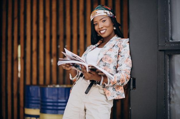 Stijlvol afrikaans amerikaans tijdschrift lezen in de straat