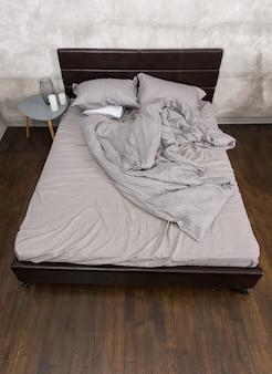Stijlvol bed met verfrommeld deken in grijze kleuren en nachtkastje met kaarsen