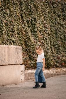 Stijlvol blond meisje in jeans en een wit t-shirt loopt door de straat. meisje 7 jaar klein model, mooi kind