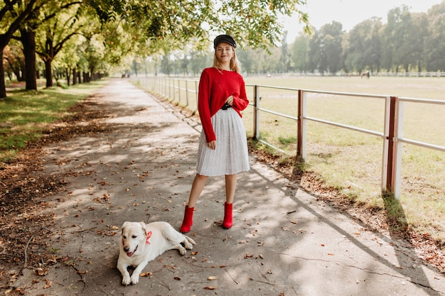 Stijlvol blond meisje met zwarte hoed en witte rok poseren met haar hond op het parkpad.