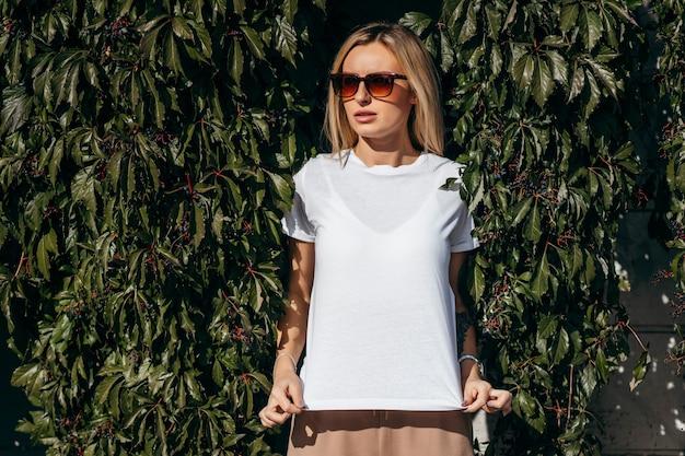 Stijlvol blond meisje wit t-shirt en bril dragen