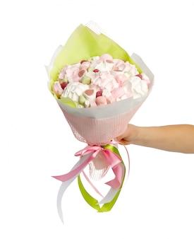 Stijlvol boeket van marshmallows in een vrouwelijke hand op wit