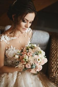 Stijlvol boeket van roze en witte bloemen in de handen van het mooie model meisje in trendy trouwjurk