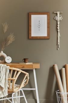Stijlvol bohemien interieur van thuiskantoorruimte met houten bureau rotan fauteuil bruin posterframe macrame kantoorbenodigdheden lampdecoratie en elegante persoonlijke accessoires in huisdecor