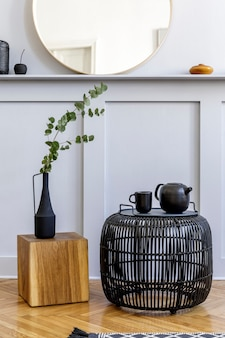 Stijlvol concept in woonkamer interieur met zwarte rotan salontafel, ronde spiegel, bloemen in vaas, lantaarn, plank, houten kubus en elegante persoonlijke accessoires in modern interieur.