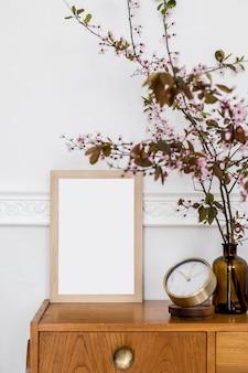 Stijlvol concept van home enscenering met posterframe, design houten commode, lentebloemen, gouden klok en elegante accessoires in een modern woonkamerinterieur.