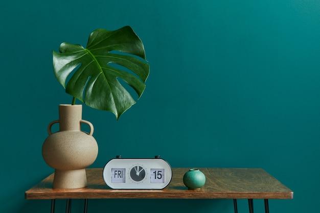 Stijlvol concept van woonkamer interieur met walnoot tafel, tropisch blad in vaas,