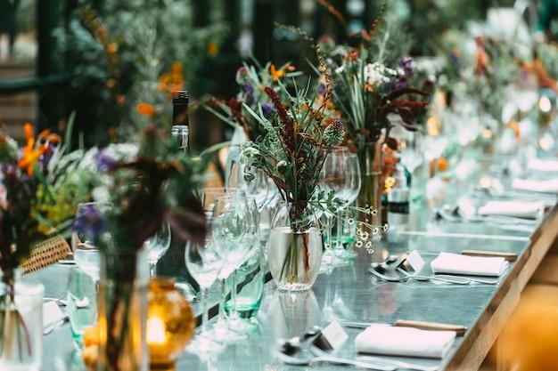 Stijlvol diner in de buitenlucht. gedecoreerde tafel met prachtige wilde bloemboeketten
