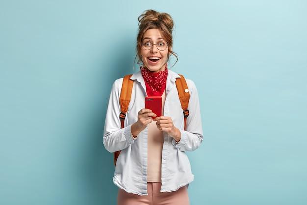 Stijlvol duizendjarig hipster meisje gaat naar school, heeft altijd contact, houdt mobiele telefoon vast, controleert melding, draagt grote ronde bril, casual shirt en rode bandana op nek, draagt rugzak