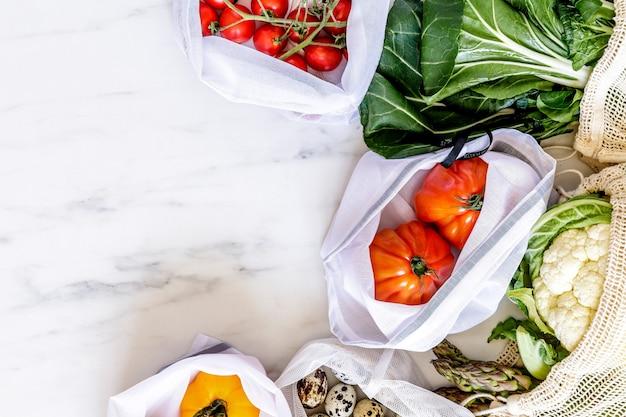 Stijlvol eco-concept op de marmeren tafel met afvalvrije zakken, noten, zaden, eieren, kruiden, bio-groenten en vers fruit. zorg dragen voor de aarde. stop met plastiek. ruimte kopiëren.