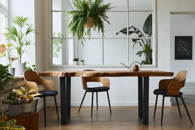 Stijlvol en botanie interieur van eetkamer met design ambachtelijke houten tafel, stoelen, veel planten, groot raam, posterkaart en elegante accessoires in modern interieur. sjabloon. Premium Foto