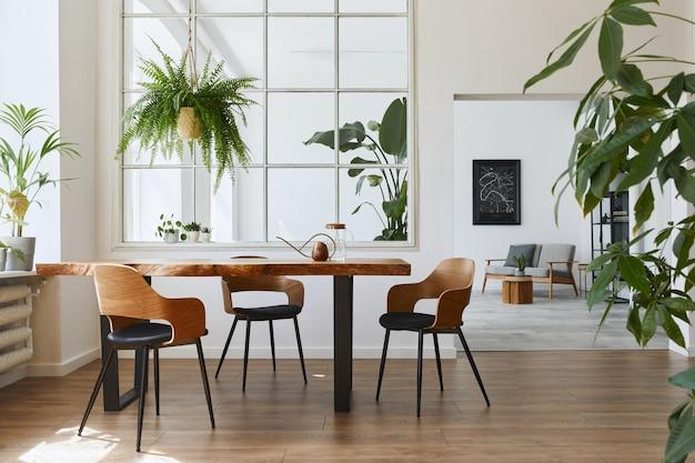 Stijlvol en botanisch interieur van eetkamer met design ambachtelijke houten tafel, stoelen, veel planten, groot raam, kaart en elegante accessoires in modern interieur..
