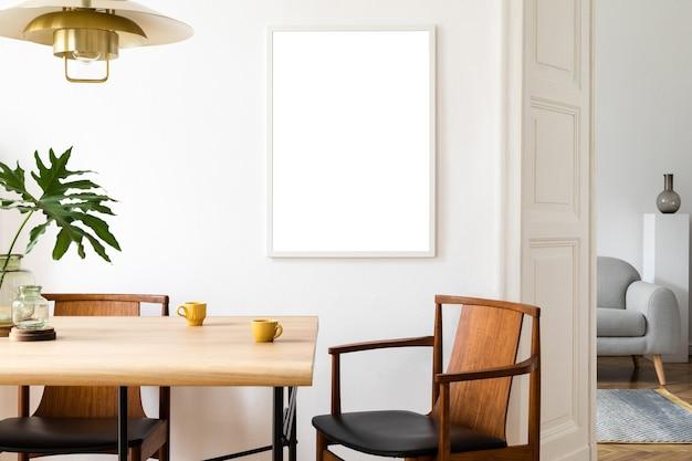 Stijlvol en eclectisch eetkamerinterieur met mock-up posterkaart, tafelontwerpstoelen, gouden hanglamp en elegante bank in de tweede ruimte. witte muren, houten parket. tropische bladeren in vaas.