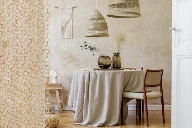 Stijlvol en elegant eetkamerinterieur met eettafel, design stoelen, rotan hanglampen, droogbloemen in vazen, meubels, decoratie en elegante persoonlijke accessoires in een gezellig interieur.