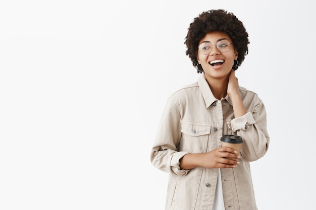 Stijlvol en gelukkig afrikaans amerikaans meisje met krullend haar, nek zachtjes aanraken en hardop lachen vreugdevol, starend naar links, koffie drinken en een interessant gesprek hebben
