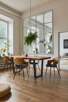 Stijlvol en gezellig interieur van eetkamer met design ambachtelijke houten tafel, stoelen, planten, fluwelen bank, posterkaart en elegante accessoires in modern interieur.