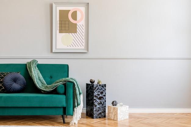 Stijlvol en luxe woonkamerinterieur met elegante groene fauteuil, retro tafels, designlampen, chique accessoires, gouden spiegel en mock-up frames op de grijze muur. sjabloon.
