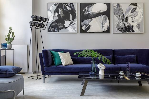 Stijlvol en modern woonkamerinterieur met blauwe fluwelen bank, schilderijen, designmeubels, plant, tafel, decoratie, betonnen vloer, elegante persoonlijke accessoires in woondecoratie.