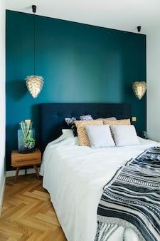 Stijlvol en modern zonnig slaapkamerinterieur met klein houten nachtkastje, tuin in een pot, wit beddengoed, kleuren kussens en deken