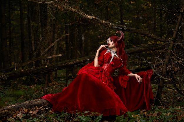 Stijlvol en modieus modelmeisje in het beeld van maleficent poseren onder mystiek bos - sprookjesverhaal, cosplay. halloween.