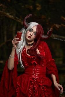 Stijlvol en modieus modelmeisje in het beeld van maleficent poseren onder mystiek bos - sprookjesverhaal, cosplay