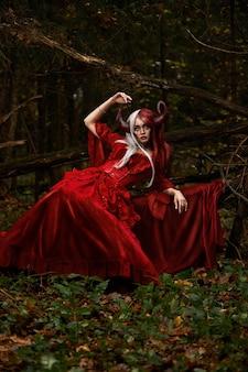 Stijlvol en modieus modelmeisje in het beeld van maleficent poseren onder mystiek bos