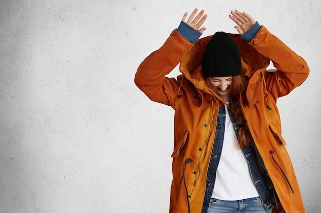 Stijlvol en modieus roodharige model in rode winterjas en trendy zwarte hoed die haar handen boven het hoofd houdt
