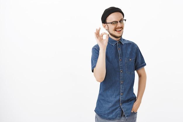 Stijlvol en vriendelijk ondersteunend mannelijk model met baard die knipoogt en vrolijk glimlacht en perfect of uitstekend gebaar toont