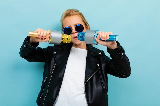 Stijlvol europees meisje in zonnebril zingen in twee microfoons op lichtblauw
