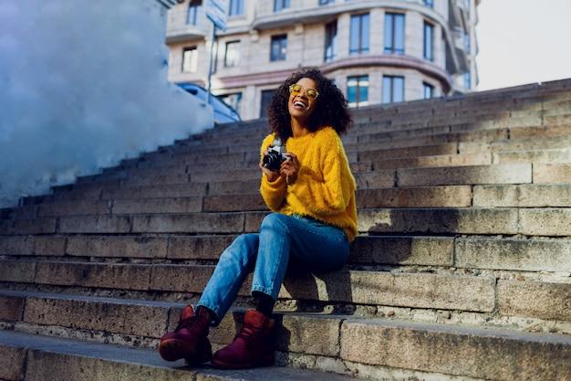 Stijlvol geïnspireerde vrouwelijke student zittend op de trap en kijkt ernaar uit. .