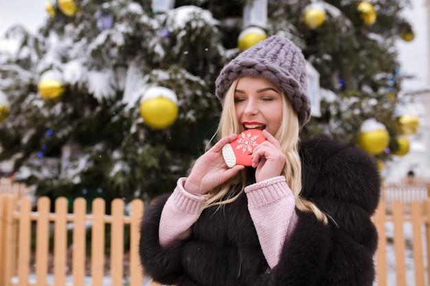 Stijlvol geklede blonde vrouw in grijze gebreide muts bijt heerlijke peperkoek tegen de kerstboom in de stad