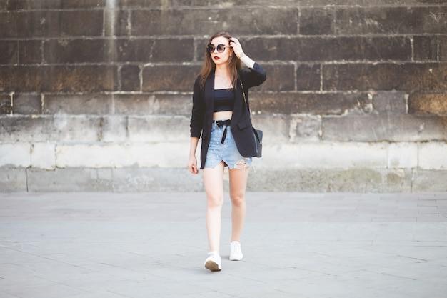 Stijlvol geklede jonge brunette die door de stad loopt