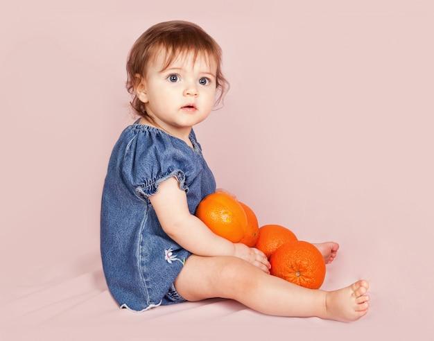 Stijlvol gekleed meisje met sinaasappel poseren in de studio op roze