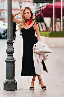 Stijlvol gelooid meisje in zwarte jurk en rode halsdoek poseren in de buurt van ijzeren lantaarnpaal