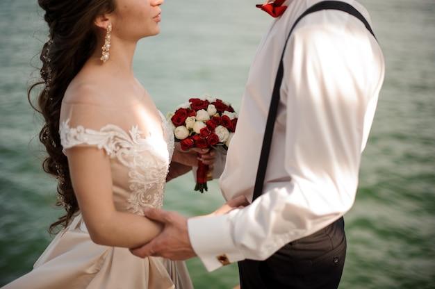 Stijlvol getrouwd stel met een bruiloftsboeket omhelst op de achtergrond van de azuurblauwe zee