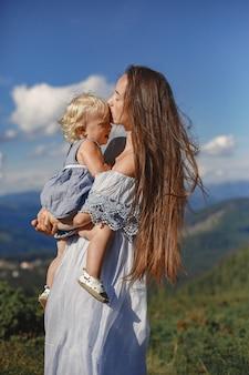 Stijlvol gezin in de bergen. moeder en dochter op een hemelachtergrond. vrouw in een witte jurk.