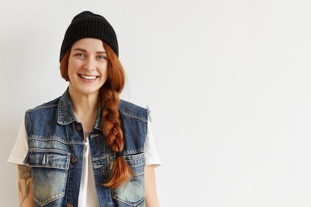Stijlvol glimlachend roodharig meisje met vlecht die zwarte hoed en mouwloos spijkerjasje draagt