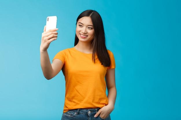 Stijlvol, goed uitziend aziatisch schattig meisje houdt smartphone vast en praat video-oproep glimlachend kijkt in grote lijnen naar het telefoonscherm, neemt selfie, voelt zich mooi, praat met volgers online sociale media, blauwe achtergrond.